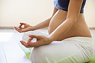 Prenatal yoga, woman meditating in lotus position - ZEDF00337
