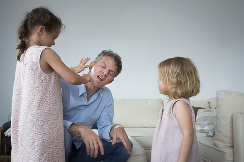 Daughter sticking band aid on father's cheek - JTLF00114