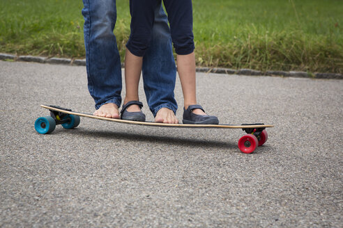 Father and daughter longboarding in garden - JTLF00117