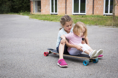 Two sisters sitting on longboard - JTLF00120