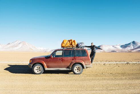 Bolivia, Altiplano, Eduardo Avaroa Andean Fauna National Reserve, Man hanging from a 4x4 car - GEMF01075