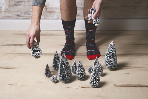 Young man wearing winter socks placing Christmas tree decoration on the floor - RTBF00394