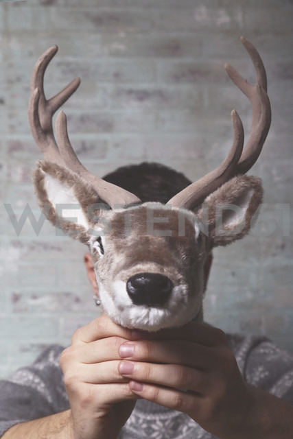 Young man holding artificial deer head  in front of his face - RTBF00403