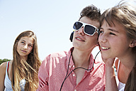 Three teenage friends with headphones outdoors - FSF00518