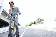 Teenage boy on bicycle talking on cell phone - FSF00548