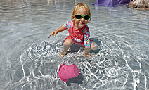 Clothed little girl with sunglasses  playing in water - LHF00506