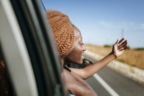 Young woman leaning out of car window - KIJF00790