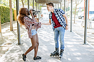 Young woman filming her boyfriend on inline skates with an old-fashioned camera - KIJF00814