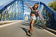 Young woman on skateboard on a bridge - KIJF00817