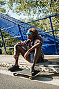 Young woman with skateboard sitting on a bridge - KIJF00820