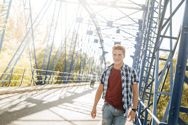 Smiling young man walking on a bridge - KIJF00823