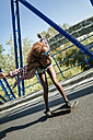 Happy young woman on skateboard on a bridge - KIJF00826
