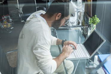 Young man working with laptop at desk in a modern office - TCF05111