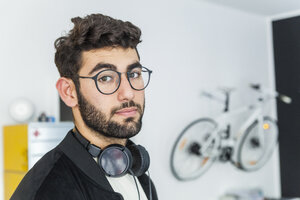 Portrait of man with glasses and headphones in a modern office - TCF05123