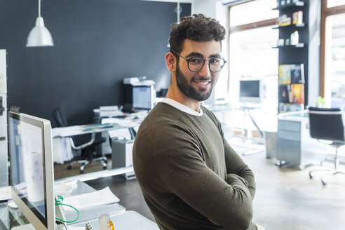 Portrait of smiling man in a modern office - TCF05126