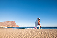Spain, Tenerife, young female surfer on the beach - SIPF00882
