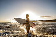 Spain, Tenerife, young female surfer at sunset - SIPF00885