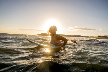 Spain, Tenerife, young female surfer at sunset - SIPF00888
