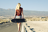 Spain, Tenerife, blond young skater with skateboard walking on road - SIPF00894