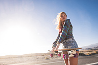Spain, Tenerife, blond young skater with skateboard against the sun - SIPF00915