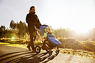 Father and son in buggy on a walk in forest - MFF03365