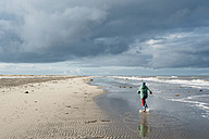 Denmark, Skagen, boy in winter clothes running on beach - MJF02012