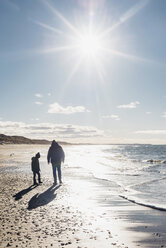 Denmark, Hirtshals, father and son walking on beach in backlight - MJF02066