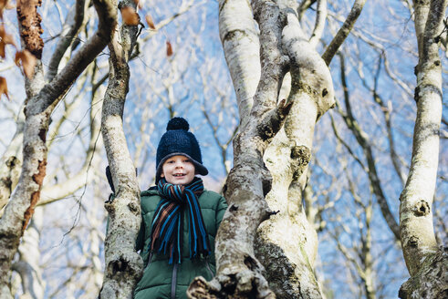 Boy climbing on a tree in winter clothes - MJF02069