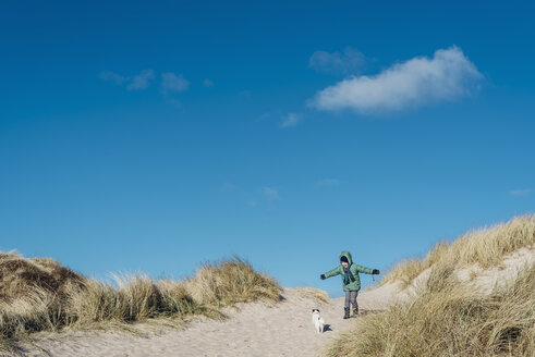 Denmark, Bulbjerg, boy in winter clothes with dog in dunes - MJF02072