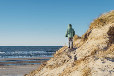 Denmark, Bulbjerg, boy in winter clothes walking in dunes - MJF02075