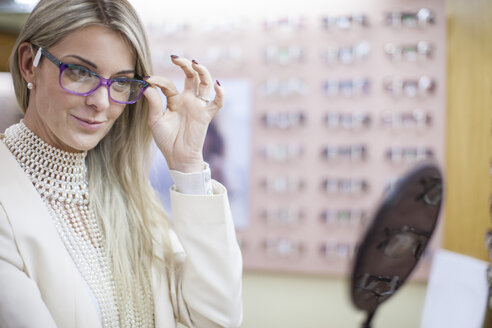 Blond woman selecting new glasses in opticians shop - ZEF10409