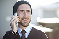 Young man wearing beanie talking on cell phone - ZEF10475