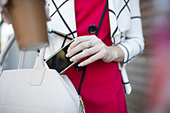 Woman with takeaway coffee putting phone in handbag - ZEF10484