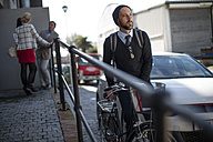 Man pushing bicycle on city street - ZEF10496