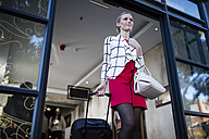 Young woman pulling suitcase out of building front door - ZEF10499