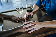 Close-up of a couple holding hands in restaurant - KIJF00834