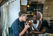 Young couple in a bar clinking glasses seen from behind window - KIJF00840