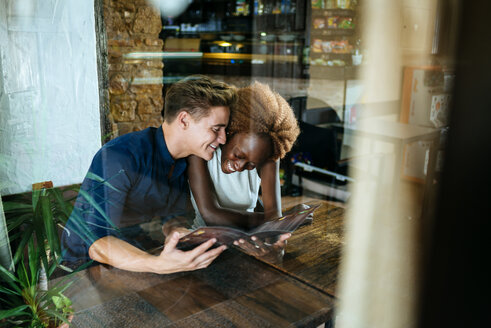 Young couple looking at a restaurant menu seen through a window - KIJF00846