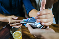 Close-up of man paying with credit card in restaurant - KIJF00849