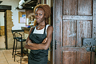 Portrait of young waitress at the door of a bar - KIJF00855