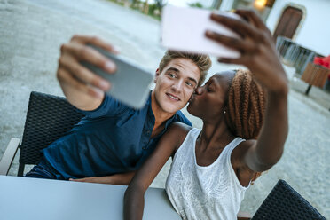 Young couple taking selfies at outdoor cafe - KIJF00858