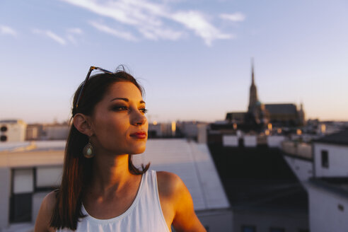 Austria, Vienna, young woman relaxing on rooftop at sunset with Stephansdom in the background - AIF00372