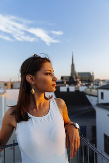 Austria, Vienna, young woman on rooftop at sunset with Stephansdom in the background - AIF00375