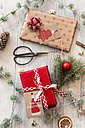 Christmas decoration, scissors and wrapped presents on wood - SARF02949