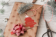 Christmas decoration, scissors and wrapped presents on wood - SARF02952