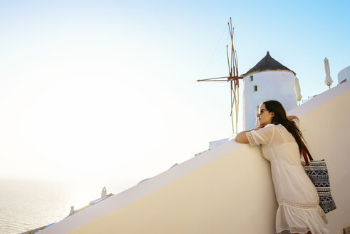 Greece, Santorini, Oia, woman leaning on a wall enjoying the sunset - GEMF01087