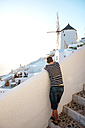 Greece, Santorini, Oia, back view of man leaning on a wall enjoying sunset - GEMF01090