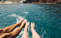 Greece, Santorini, legs of a couple in front of the sea - GEMF01102