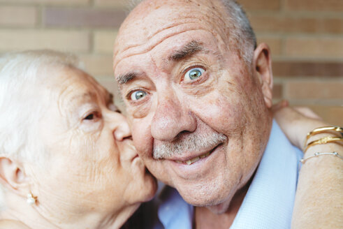 Senior man pulling funny face while his wife kissing him - GEMF01105