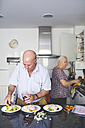 Senior couple preparing food in the kitchen - GEMF01111